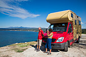 Couple in front of red motorhome overlooking bay, Pylos, Peloponnese, Greece