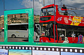 Reflection of Hop on Hop off City Sightseeing Gozo bus in tour bus window, Mgarr, Gozo, Malta