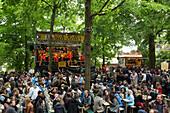 People sit outside in beer garden and enjoy live music at the Erlanger Bergkirchweih beer festival and fair, Erlangen, Franconia, Bavaria, Germany