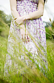 Woman standing in tall grass, cropped