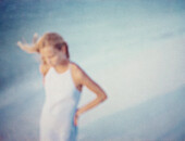 Woman walking alone on beach, defocused