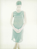 Young woman standing with hands clasped, overexposed