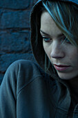 Woman in hooded sweatshirt pensively looking away