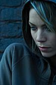 Woman in hooded sweatshirt pensively looking away