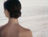 Woman looking toward ocean, rear view of head and shoulders, focus of beach in background