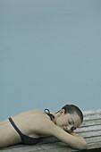 Young woman sunbathing in bikini beside pool