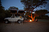 Family around a campfire, off-road vehicle with roof top tent in foreground, Purros Camp, Hoarusib, Namib desert, Nambia
