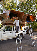 Boys standing on a ladder to a roof tent on a off-road vehicle, Nata, Nxai Pan National Park, Botswana