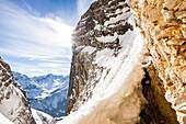 Skibergsteiger seilt sich ab, Neue-Welt-Abfahrt, Zugspitzmassiv. Im Hintergrund Mieminger Gebirge, Ehrwald, Tirol, Österreich