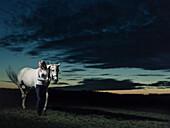 Girl standing next to her horse at dusk, Freising, Bavaria, Germany