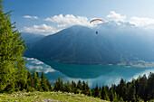 Gleitschirmflieger startet vom Zwölferkopf über dem Achensee, im Hintergrund Rofangebirge, Pertisau, Tirol, Österreich