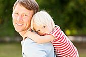 two-year-old girl on her father's back, Speyer, Rheinland-Pfalz, Germany