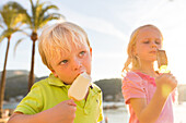 4 and 5 year old boy and girl eating, ice cream in the harbour, MR, Port de Soller, Serra de Tramuntana, Majorca, Balearic Islands, Spain, Europe