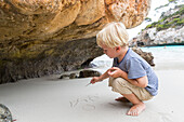 boy writing in the sand, beach at Calo des Moro, Mediterranean Sea, MR, near Santanyi, Majorca, Balearic Islands, Spain, Europe