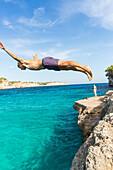 Young man diving into the turquoise blue water, Cala Sa Nau, tourist, Mediterranean Sea, near Portocolom, Majorca, Balearic Islands, Spain, Europe