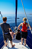 Two young women and two young men on a sailing yacht observing bottlenose dolphins (Tursiops truncatus) that are swimming close to the boat, Mallorca, Balearic Islands, Spain, Europe