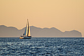 A sailing yacht at sunset, Cap Formentor with its lighthouse in the background, the northernmost point of  Mallorca, Balearic Islands, Spain, Europe