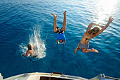 Two young women and a young man are jumping from the stern of a sailing yacht into the clear blue sea, Mallorca, Balearic Islands, Spain, Europe