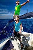 A young woman is standing at the steering wheel, rudder of a sailing yacht and is steering, a young man is standing behind her, Mallorca, Balearic Islands, Spain, Europe