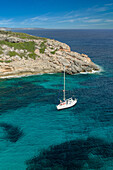 A sailing yacht anchors in a lonely bight with clear blue water, Mallorca, Balearic Islands, Spain, Europe