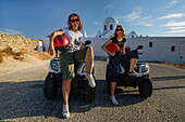 Two young women sitting on quad bikes and smiling into the camera, Greek Islands, Aegean, Cyclades, Greece