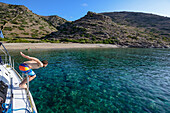 Man diving off a sailing yacht into a lonely bay of the greek island of Kithnos, Kolona, Aegean, Cyclades, Greece