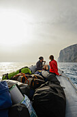 Young woman and young man are sitting with trekking gear in the front of an inflatable boat that will bring them back to the starting point of the Selvaggio Blu, Golfo di Orosei, Sardinia, Italy, Europe