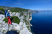 A young woman with trekking gear hiking along the mountainous coast above the sea, Selvaggio Blu, Sardinia, Italy, Europe