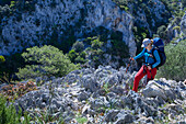 A young woman with trekking gear hiking through the mountainous coastal landscape, Selvaggio Blu, Sardinia, Italy, Europe