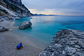 A young women cooking dinner on the beach of Cala Goloritze by the sea, Golfo di Orosei, Selvaggio Blu, Sardinia, Italy, Europe