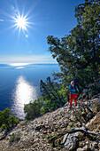 A young woman with trekking gear hiking along the mountainous coast above the sea, Golfo di Orosei, Selvaggio Blu, Sardinia, Italy, Europe
