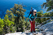 A young woman with trekking gear abseiling in the mountainous coastal landscape above the sea, Golfo di Orosei, Selvaggio Blu, Sardinia, Italy, Europe