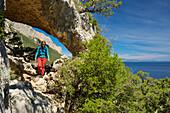 A young woman with trekking gear hiking through the rock arch Arcu su Feilau at the mountainous coast above the sea, Golfo di Orosei, Selvaggio Blu, Sardinia, Italy, Europe