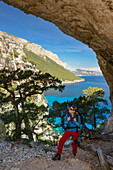 A young woman with trekking gear hikes through the rock arch Arcu su Feilau at the mountainous coast above the sea, Golfo di Orosei, Selvaggio Blu, Sardinia, Italy, Europe