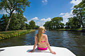 Young blonde woman wearing a bikini relaxes on deck of a Le Boat Royal Mystique houseboat on the Plassendale - Niuewpoort canal, near Bruges, Flemish Region, Belgium