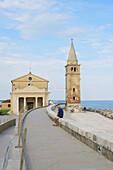 Man on a wall near a church, Madonna dell' Angelo, Caorle, Region Veneto, Adriatic, Italy, Europe