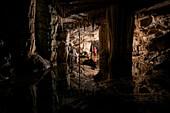 Hiker exploring stalactites in cave, Loz, Notranjska, Slovenia