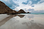 Rocky coastline reflected in still beach surf, Qalansyia, Socotra, Yemen