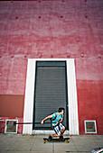 Caucasian man riding skateboard with land paddle, Los Angeles, California, USA