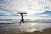 Caucasian man jumping with surfboard on beach, Los Angeles, California, USA