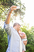 Caucasian father taking cell phone picture with baby in backyard, Los Angeles, California, USA