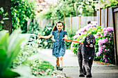 Mixed race girl walking dog on suburban sidewalk, Seattle, WA, USA