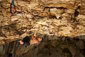 Climber hanging from rocky cave ceiling, Rodellar, Aragon, Spain