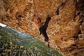 Climber hanging from rock formation, Rodellar, Aragon, Spain