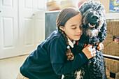 Mixed race girl hugging dog, Seattle, WA, USA
