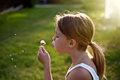 Caucasian girl blowing seeds off dandelion, Charlevoix, Michigan, USA