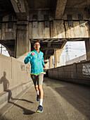 Caucasian man running in urban tunnel, Los Angeles, California, USA