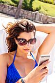 Mixed race woman using cell phone on beach, Puerto Vallarta, Jalisco, Mexico