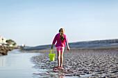 Caucasian girl carrying bucket on beach, Brunswick, Georgia, USA
