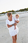 Caucasian mother carrying baby on beach, Brunswick, Georgia, USA